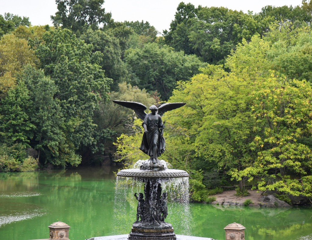 Bethesda Fountain Angel with lake and trees in the background.